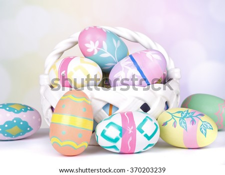 Assortment of Painted Easter eggs and white basket on a colorful background - stock photo