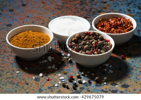 assortment of pepper, different spices and sea salt in bowl on a dark background, horizontal