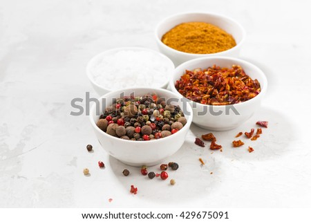 assortment of pepper, salt and spices in bowls on white table, horizontal - stock photo