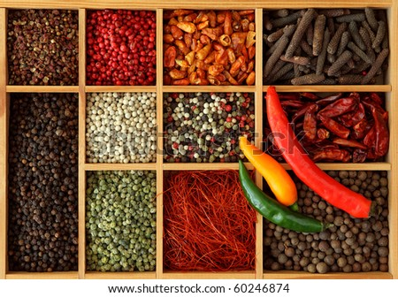 Assortment of peppercorns and chili in wooden box - stock photo