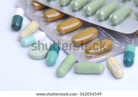 assortment of pills and capsules of natural medicine, herbal and homeopathic isolated in white - stock photo