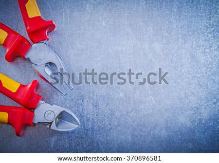 Assortment of pliers wire-cutter on metallic background electricity concept. - stock photo
