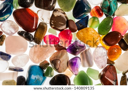 Assortment of polished semi-precious gem stones shot in the studio against white background. - stock photo