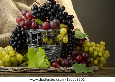 assortment of ripe sweet grapes in basket, on grey background - stock photo