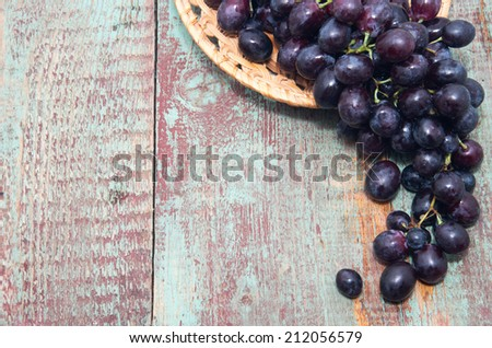 assortment of ripe sweet grapes in basket wooden background - stock photo