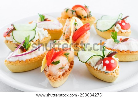 Assortment of salty mini tartlets stuffed with vegetable, shrimps and cream cheese - stock photo