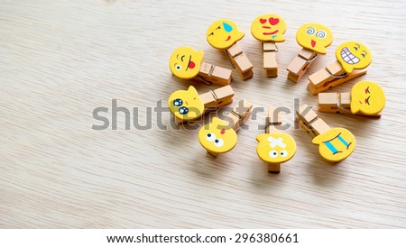 Assortment of smiley faces emoticon on clothes peg on wooden surface. Concept of emotions or meta communicative pictorial representation of a facial expression. Slightly de-focused. Copy space. - stock photo