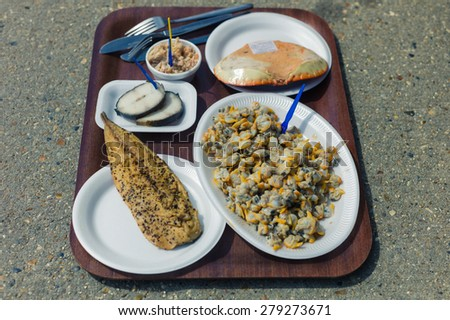 Assortment of smoked fish, crab and cockles on a tray outside - stock photo