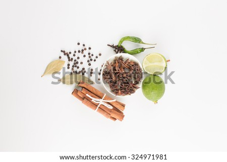 Assortment of spice,Star anise in white bowl and cinnamon,bay leave,pepper corn,clove green pepper,lime fruit over white background - stock photo