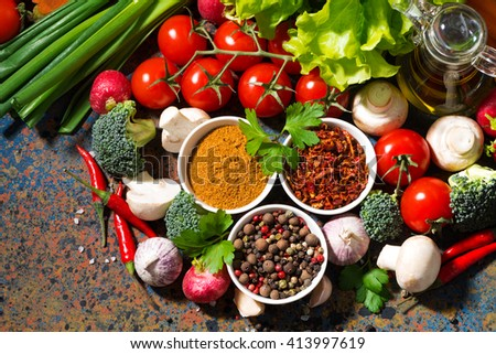 assortment of spices and fresh organic vegetables on a dark background, top view, horizontal - stock photo