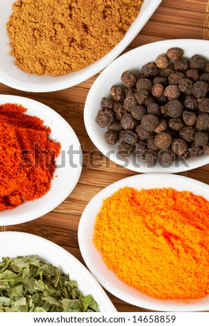 Assortment of spices in the spoons for prepare tasty food with soft shadow in the wooden background - stock photo