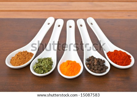 Assortment of spices in the spoons for prepare tasty food with soft shadow in the wooden background. Shallow depth of field - stock photo