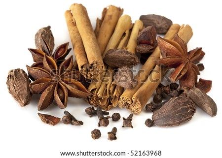 Assortment of spices, over white background.  Includes star anise, cinnamon sticks, black cardamom pods, black peppercorns, and cloves.