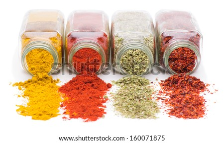 Assortment of spices spilling from glass spice jars   - stock photo