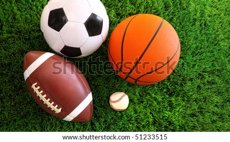 Assortment of sport balls on green grass - stock photo