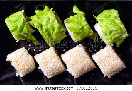 Assortment of Sushi rolls on black background - stock photo