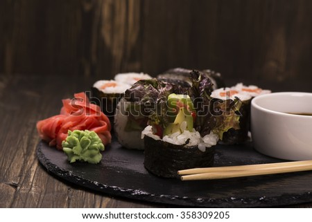 Assortment of sushi rolls with salmon and vegetables, served with soy sauce and chopsticks over grunge wooden background. Selective focus - stock photo