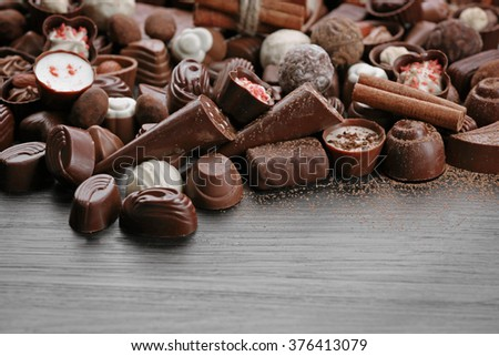 Assortment of tasty chocolate candies and cinnamon on wooden table background - stock photo