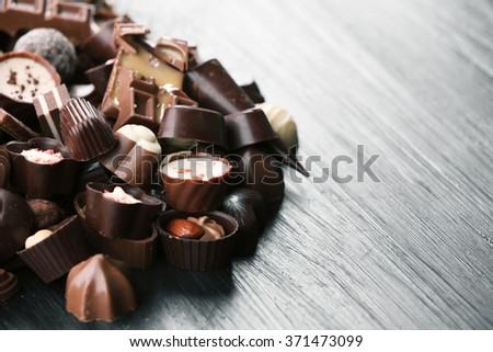 Assortment of tasty chocolate candies on wooden table background - stock photo