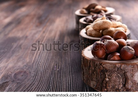 Assortment of tasty nuts on wooden background - stock photo