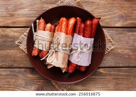 Assortment of thin sausages, and spices on plate, on wooden background - stock photo