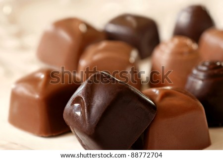 Assortment of tiny chocolate candies on decorative plate.  Macro with extremely shallow dof.  Selective focus limited to closest piece of dark chocolate. - stock photo