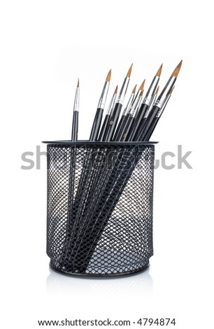 Assortment of various paintbrushes in the basket, reflected on white background - stock photo