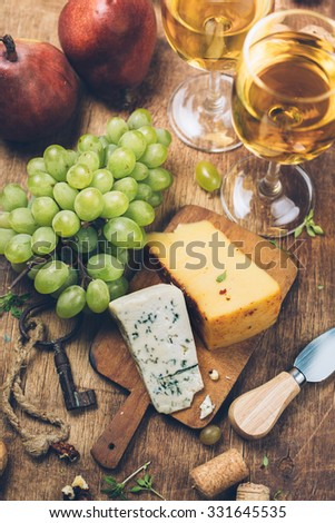 Assortment of various types of cheese on wooden board and White wine, top view - stock photo