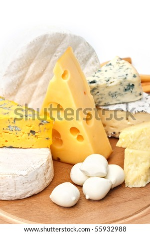 Assortment of various types of cheese on wooden board on white background - stock photo