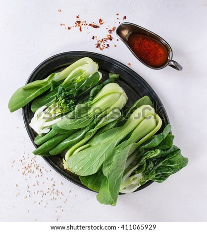 Assortment of whole and sliced raw baby bok choy (Chinese cabbage) with hot chili pepper olive oil over white stone textured background. Top view.  - stock photo