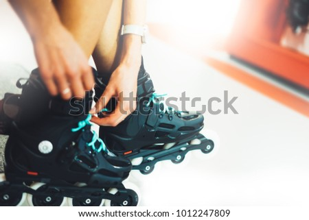 Assortment roller skates isolated in store shop, person choosing and buy color roller-skates on backgraund sun flare, healthy and activity lifestyle concept close up, girl consider sport footwear