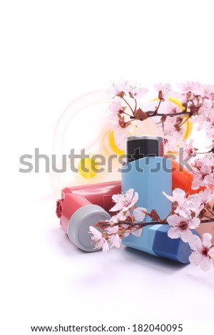 Asthma inhalers with extension tube for children and blossoming tree branches over white - stock photo