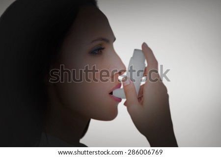 Asthmatic brunette using her inhaler against grey vignette - stock photo