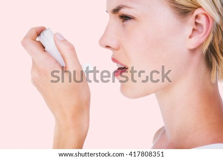 Asthmatic pretty blonde woman using inhaler against beige background - stock photo