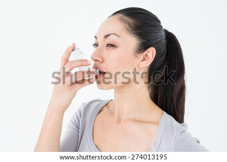 Asthmatic pretty brunette using inhaler on white background - stock photo
