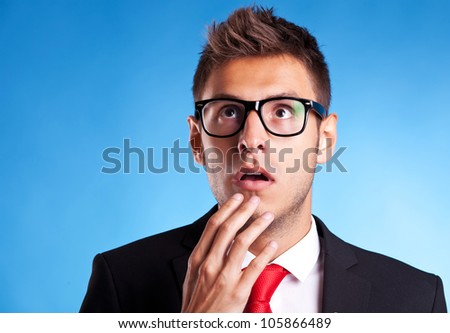 Astonished business man looking up at something on blue background - stock photo