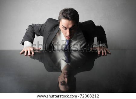 Astonished businessman looking at his reflex on a table - stock photo