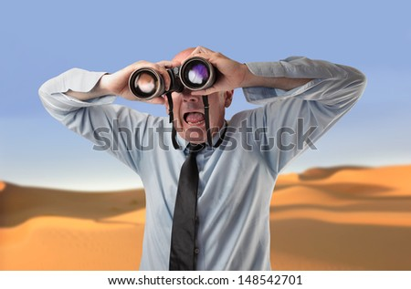 astonished businessman looking with binoculars in the desert - stock photo