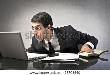 Astonished businessman staring at his laptop - stock photo