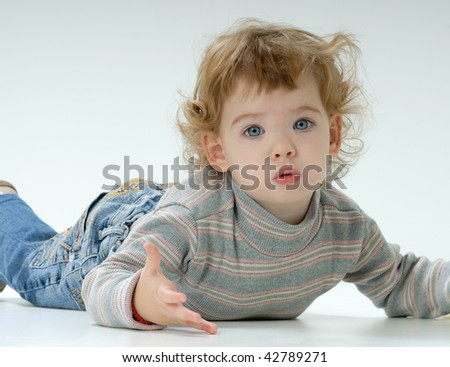astonished child lying on the floor - stock photo