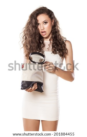 astonished girl holding a magnifying glass and looking in her handbag - stock photo