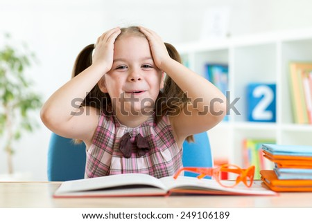 Astonished kid girl reading a book in nursery at home - stock photo