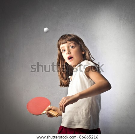Astonished little girl playing ping pong - stock photo