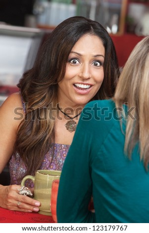 Astonished mature woman talking with friend in coffeehouse
