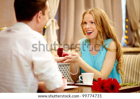 Astonished woman looking at her boyfriend showing gift at lunch