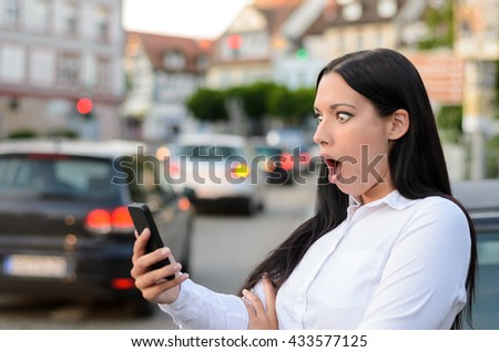 Astonished woman reading an sms on her mobile phone with a look of shock and amazement and her mouth hanging open as she stands on a busy urban street with traffic - stock photo