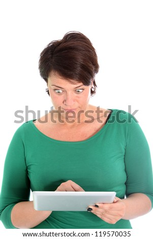 Astonished woman with a wide eyed expression of shock reading the screen of her tablet which she is handholding isolated on white - stock photo