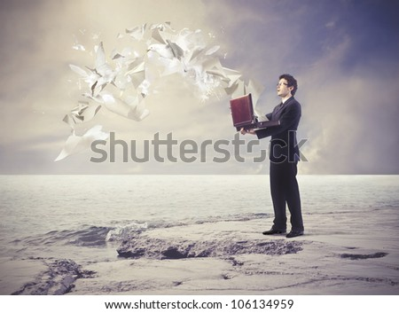 Astonished young businessman with paper sheets flying from his open briefcase - stock photo