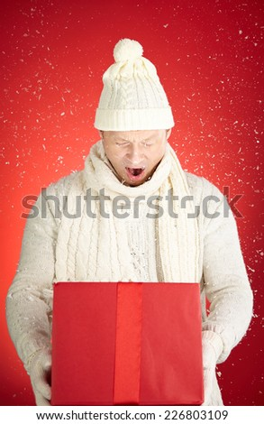 Astonished young man holding open giftbox with snowflakes flying out of it