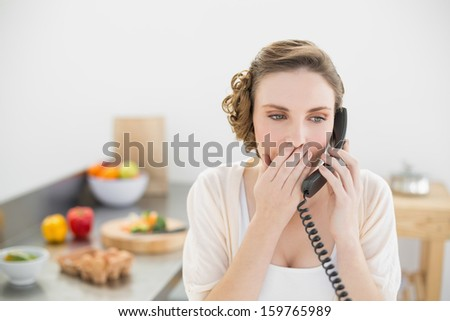 Astonished young woman phoning with her telephone in her kitchen at home - stock photo